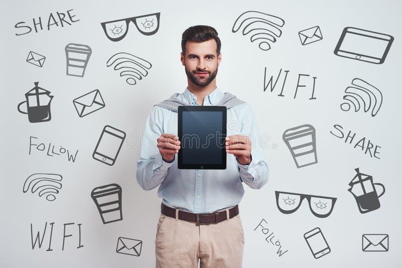 Regardez ici ! Un jeune homme beau élégant tenant et montrant l'écran d'un touchpad numérique tout en se tenant image stock