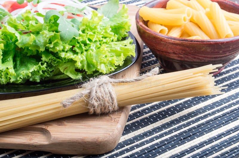 Regardez le plan rapproché sur les pâtes et les spaghetti crus avec de la salade verte images libres de droits