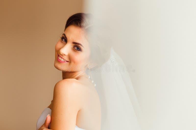 Regardez par le rideau la jeune mariée de brune avec les yeux bleus profonds photos libres de droits