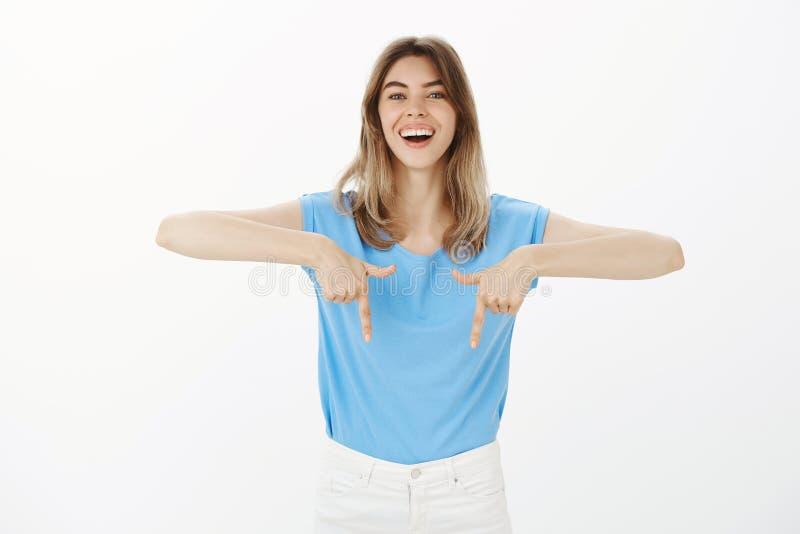 Regardez vers le bas et impressionnez-vous Portrait d'amie joyeuse belle dans le T-shirt bleu, se dirigeant vers le bas avec l'in photographie stock