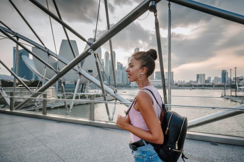 Regards de touristes de fille ? la vue incroyablement belle de la baie de Singapour Paysage urbain de la m?tropole asiatique B?ti images stock