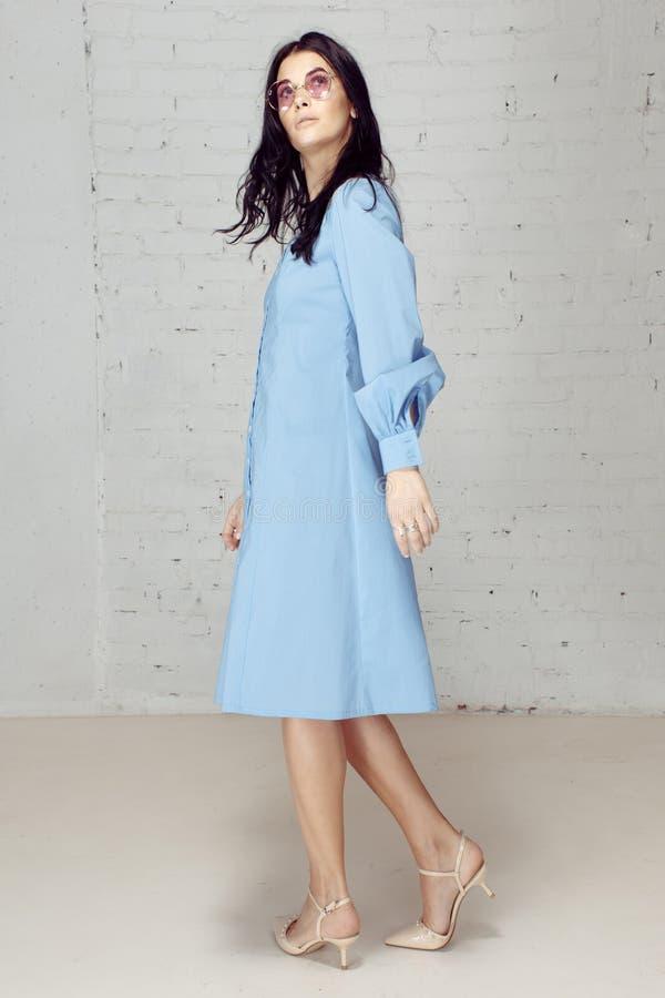 Regards enveloppés par verres bleus de rose de chemise habillée de fille images stock
