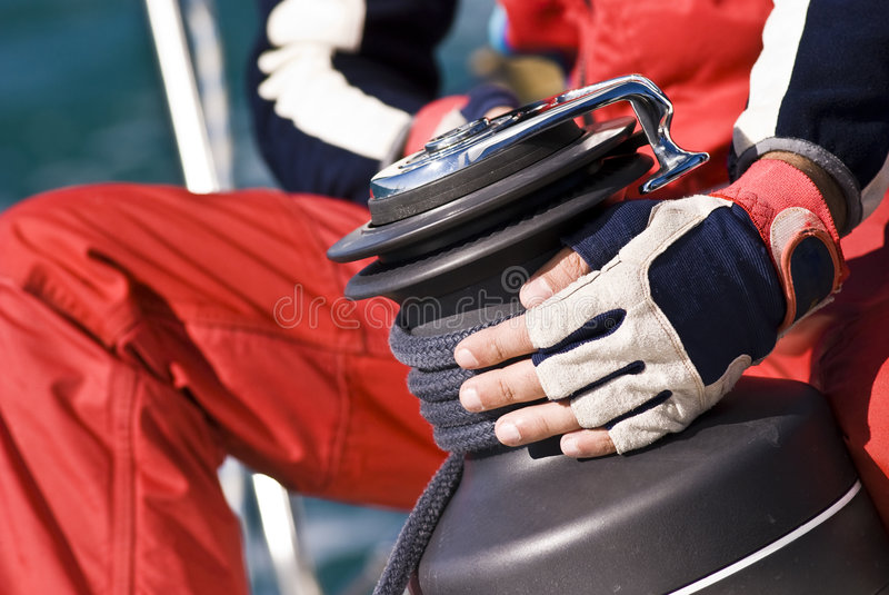 Regatta Details. Detail of a man working with hands and gloves on the winch of a sailboat during Regatta Barcolana - (Trieste, Italy 2007 stock image