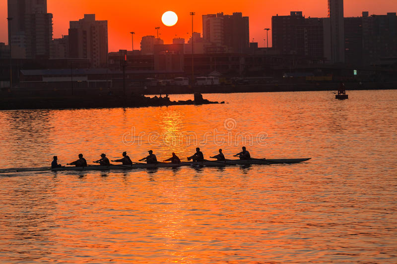Regatta Rowing Sunrise Colors. Rowing eights crew silhouetted in action on harbor waters at sunrise . Durban Rowing Club Head of the Bay Regatta on 12th July stock photo