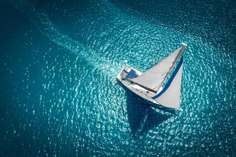 Regatta sailing ship yachts with white sails at opened sea. Aerial view of sailboat in windy condition royalty free stock photos