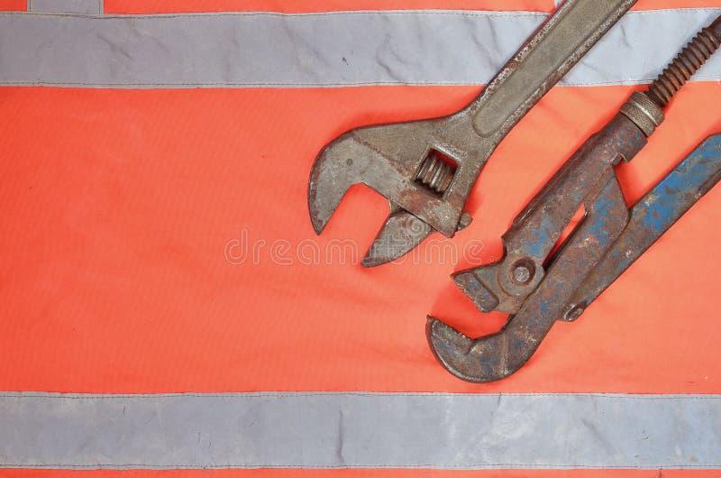 Regelbare en pijpmoersleutels tegen de achtergrond van een oranje overhemd van de signaalarbeider Stilleven verbonden aan reparat royalty-vrije stock foto's