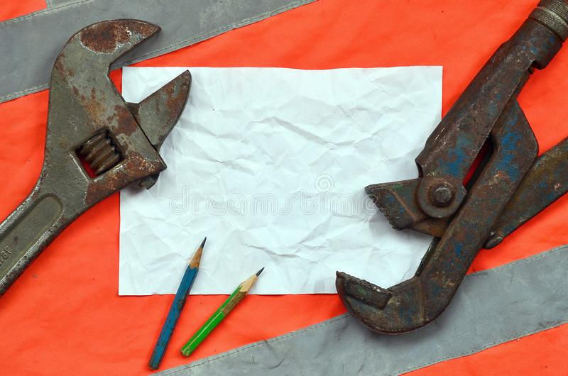 Regelbare moersleutels en een blad van document met twee potloden Stilleven verbonden aan reparatie, spoorweg of loodgieterswerk  royalty-vrije stock foto's