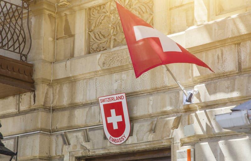 Regelen de nationale vlaggen die van Zwitserland in de wind door een gebouw in een stad vliegen, rode vlag met wit kruis royalty-vrije stock afbeeldingen