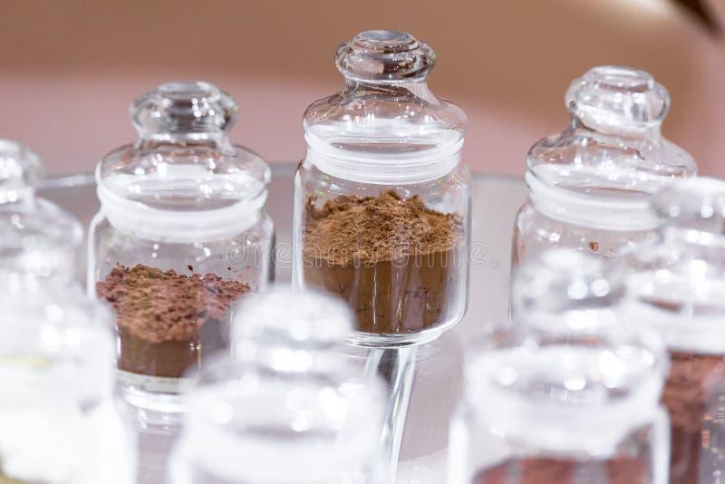 Regelmatig en alkalised cacaopoeder met darchocolade, in glaskruiken met deksels stock foto's