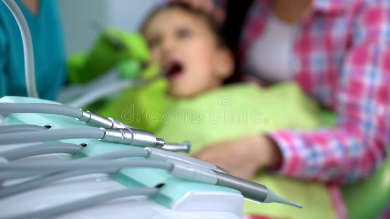 Regelmatige mondholtecontrole in moderne pediatrische tandheelkundekliniek, handpiece royalty-vrije stock afbeeldingen