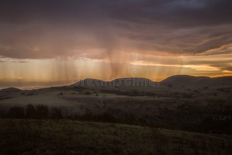Regen die op een verre berg met oranje zonsondergang vallen stock fotografie