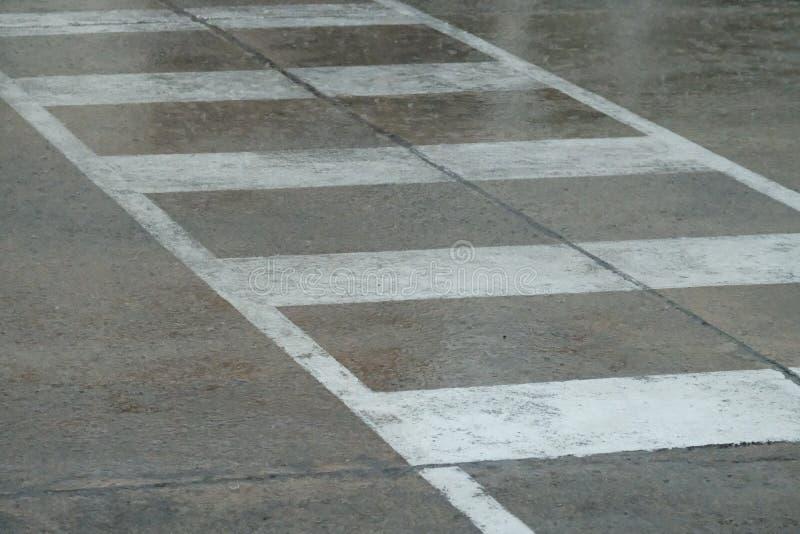 Regen an einer Reihe von weißem, an weiße Linien des Zebrastreifens auf Stadt stree liraining Die Regenzeit lizenzfreie stockfotografie