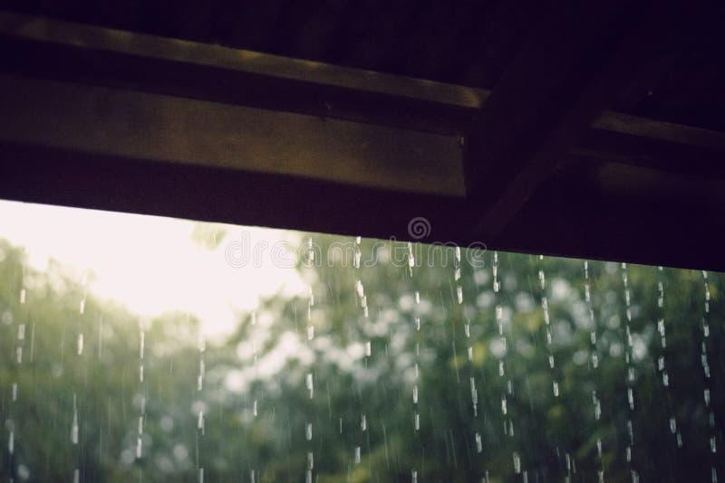 Regen vom Dach des Holzhauses lizenzfreie stockbilder