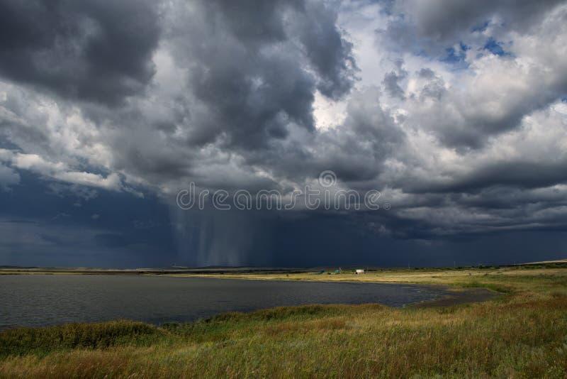 Regen von den Wolken über einem See stockfotos