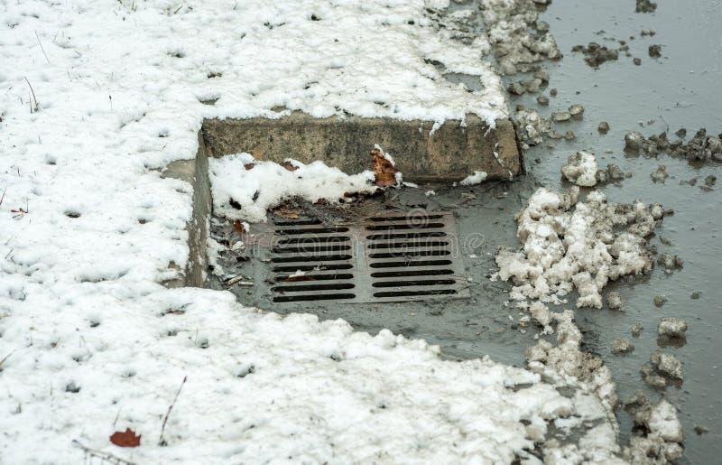 Regenabflussgosse oder -einsteigeloch auf der Straße in der Stadt für das Wasser umgeben mit Schnee im Winter stockfotos