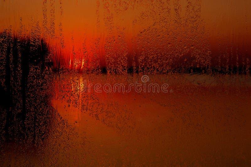 Regenachtig venster bij zonsondergang stock foto