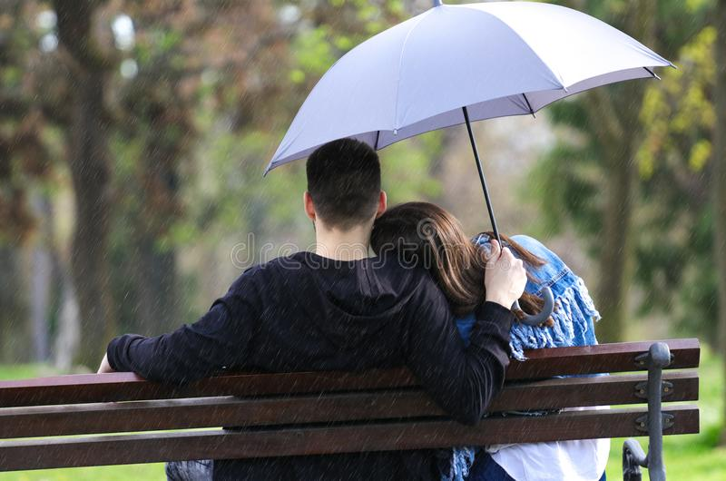 Regenachtige van het dagjongen en meisje zitting op bank en holdings blauwe umbrell royalty-vrije stock fotografie
