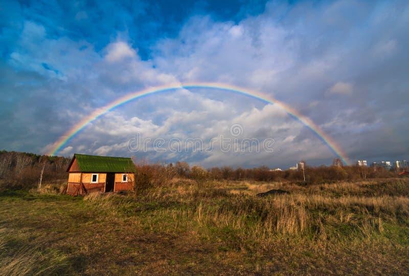 Regenbogen über dem Feld des gelben trockenen Grases und des einsamen Hauses stockfotos
