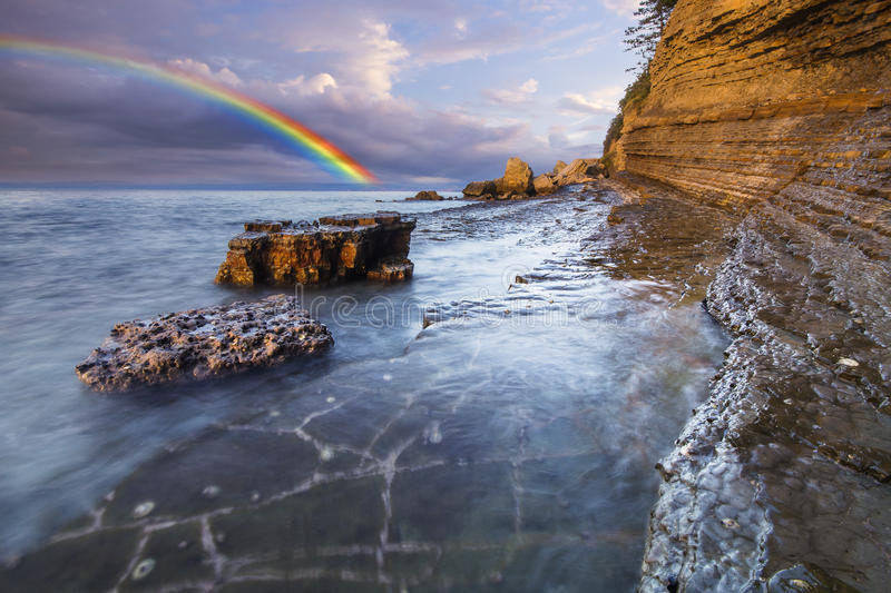 Regenbogen über der Klippe, nachdem ein Abendsturm geführt worden ist lizenzfreie stockfotografie
