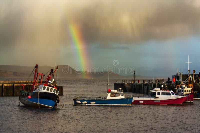 Regenbogen über Fischerbooten bei Lyme Regis lizenzfreie stockfotos