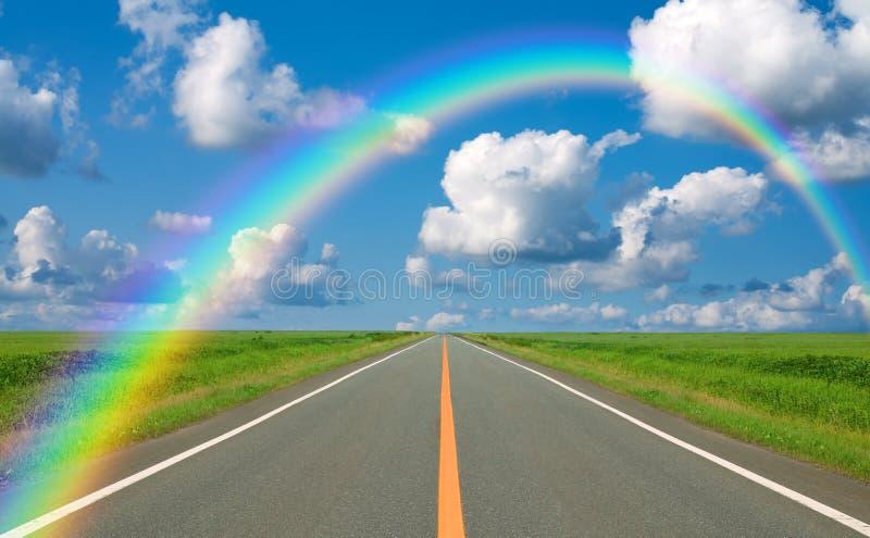 Regenbogen über gerader Straße stockbilder