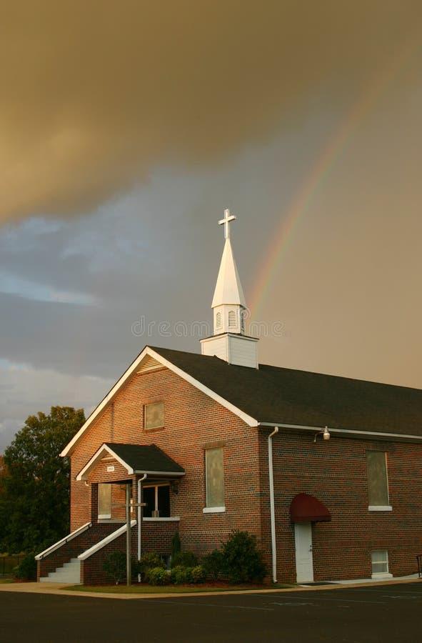 Regenbogen über Kirche lizenzfreies stockbild