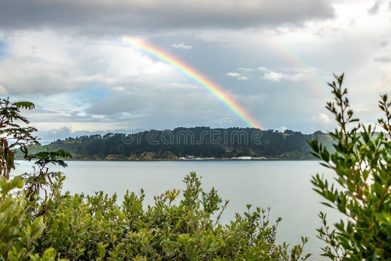 Regenbogen über Miramar Evans und Shelly Bay, Neuseeland lizenzfreie stockbilder
