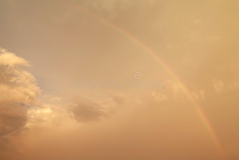 Regenbogen in den gelben Wolken stockfotos