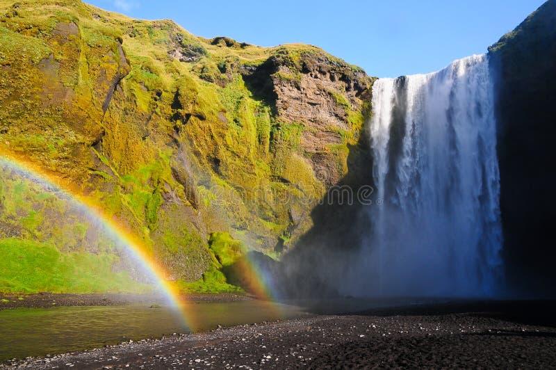 Regenbogen die door waterval Skogafoss gaan stock fotografie