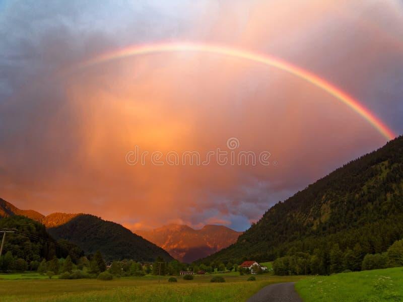 Regenbogen durch Orange bewölkte Himmel in der alpinen Landschaft stockbild