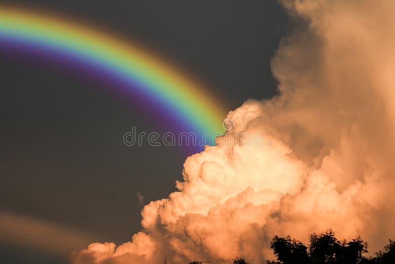 Regenbogen erscheint im Himmel nach dem Regen und der Rückseite auf Sonnenuntergangwolke lizenzfreies stockfoto