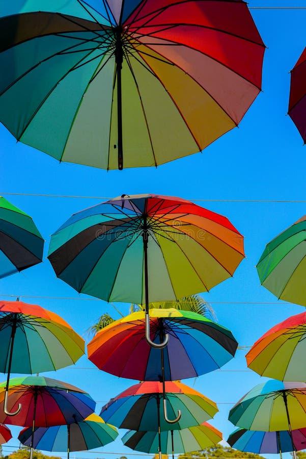 Regenbogen färbte die Regenschirme, die am vertikalen Bild des Himmels hängen stockbilder