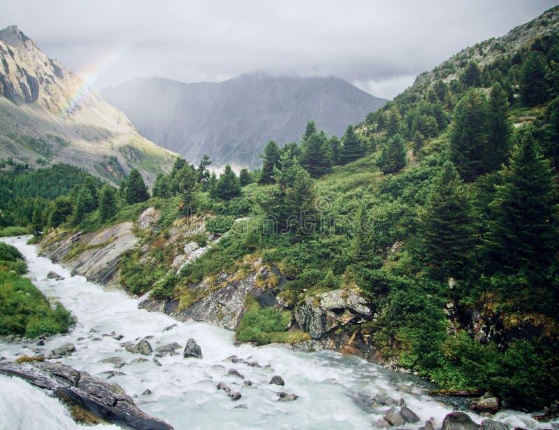 Regenbogen in het spuiten van het irrigatiewater in berg stock afbeeldingen