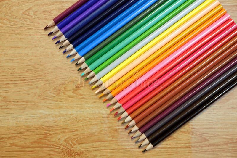 Regenbogen vom Satz farbigen Bleistiften auf einem Holztisch stockbild