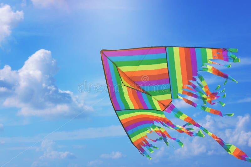 Regenbogendrachenfliegen im blauen Himmel mit Wolken Freiheit und Sommerferien lizenzfreies stockfoto