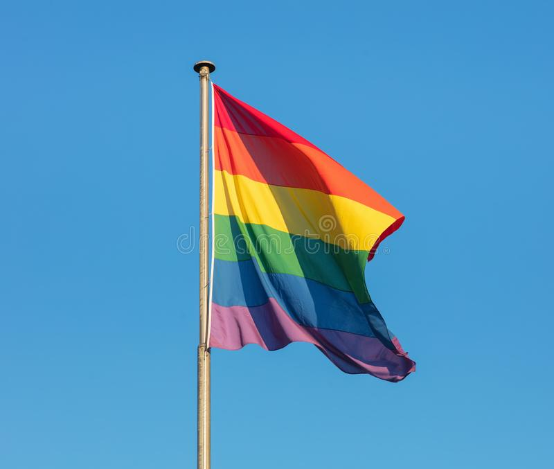 Regenbogenflagge der LGBT-Bewegung gegen blauen Himmel stockfotografie