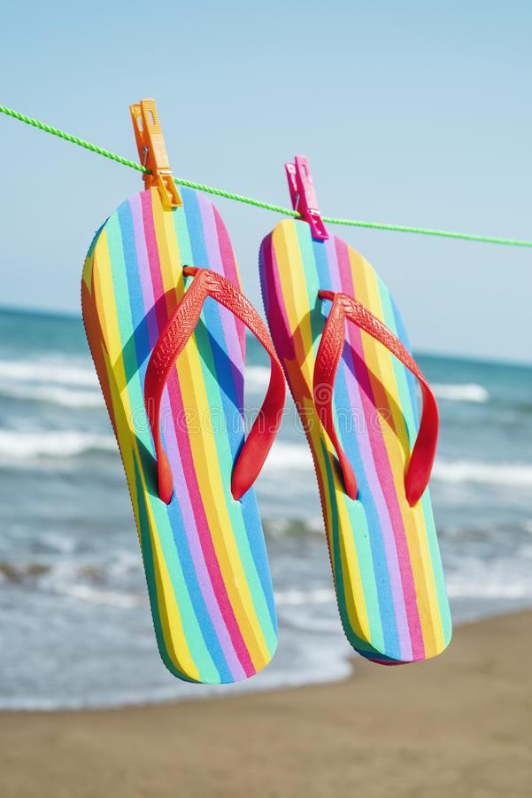 Regenbogenflipflops, die an einer Wäscheleine hängen stockfotografie