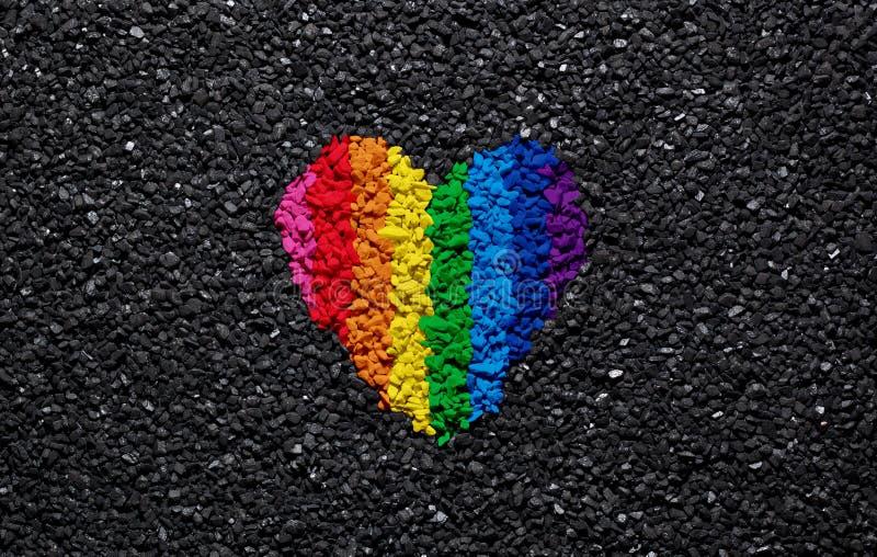 Regenbogenherz auf schwarzem Hintergrund, Kies und Schindel, LGBT-Farben, Liebestapete, Valentinsgruß lizenzfreie stockfotografie