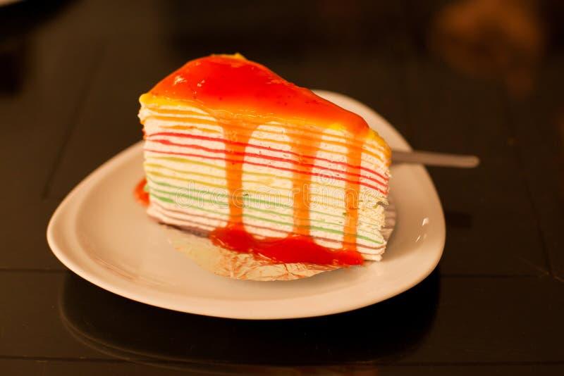 Regenbogenkreppkuchen auf weißer Platte auf hölzerner Tabelle stockfoto