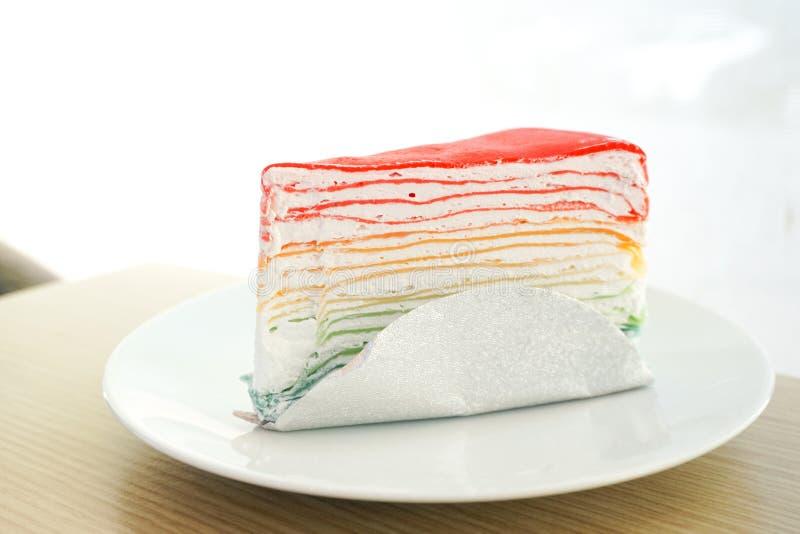 Regenbogenkreppkuchen auf weißer Platte auf Holztisch stockfoto
