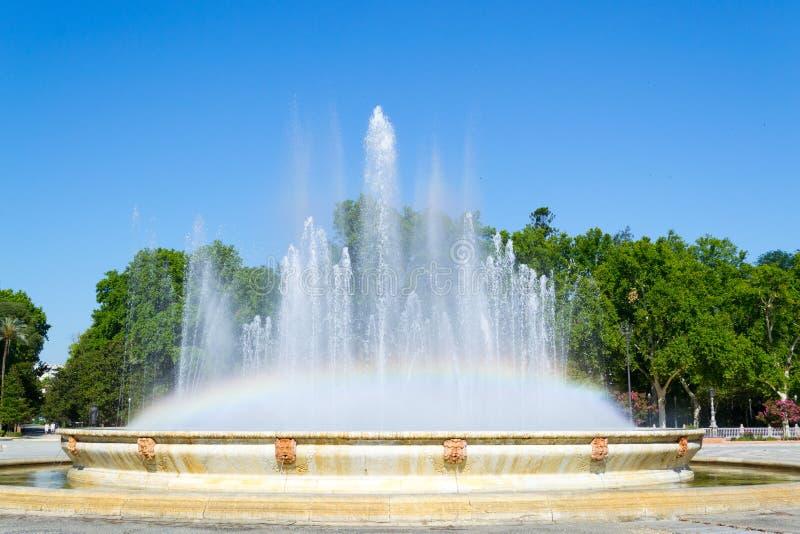 Regenboog bij de vierkante fontein van Spanje stock afbeelding