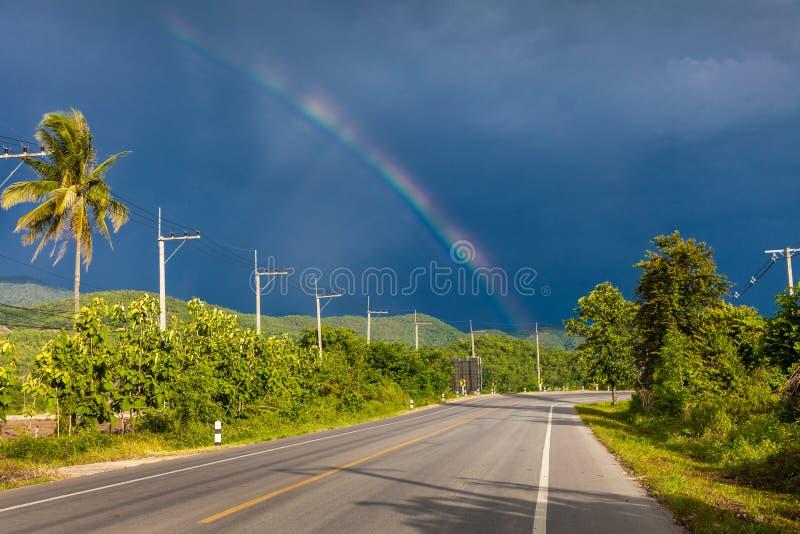 Regenboog in de stormachtige hemel over de weg royalty-vrije stock afbeeldingen