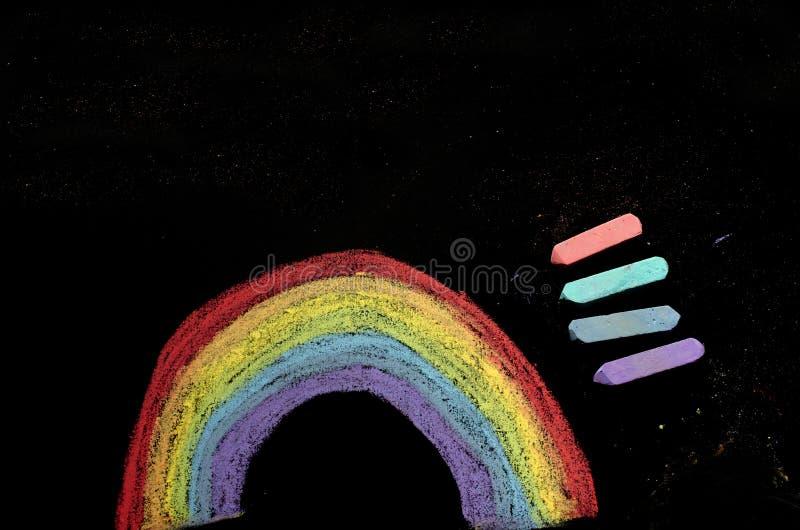 Regenboog en krijt dat op bord wordt getrokken royalty-vrije stock afbeeldingen