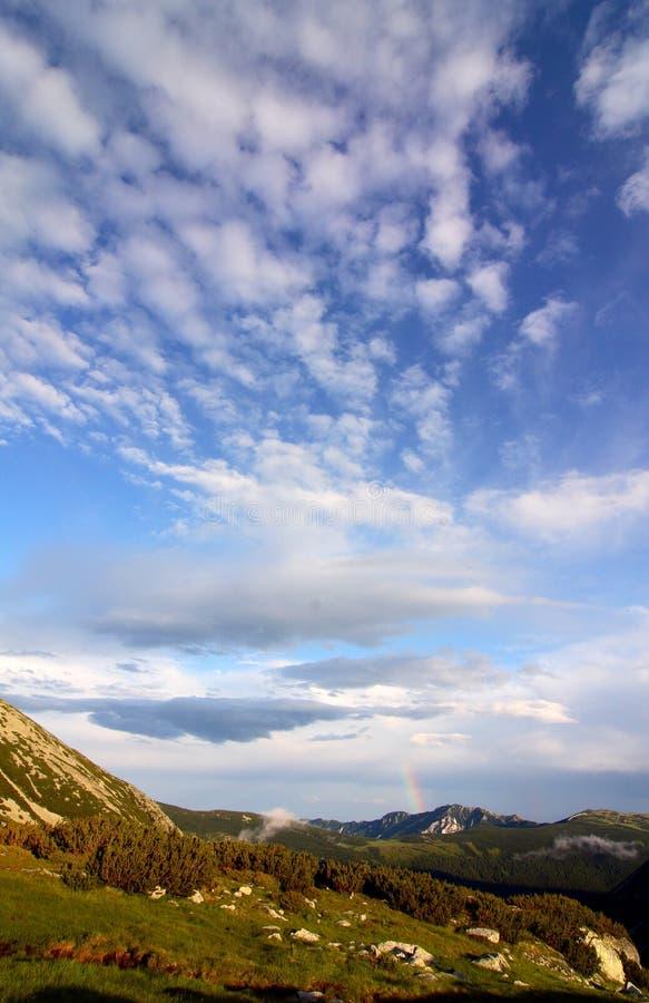 Regenboog en wolken stock fotografie