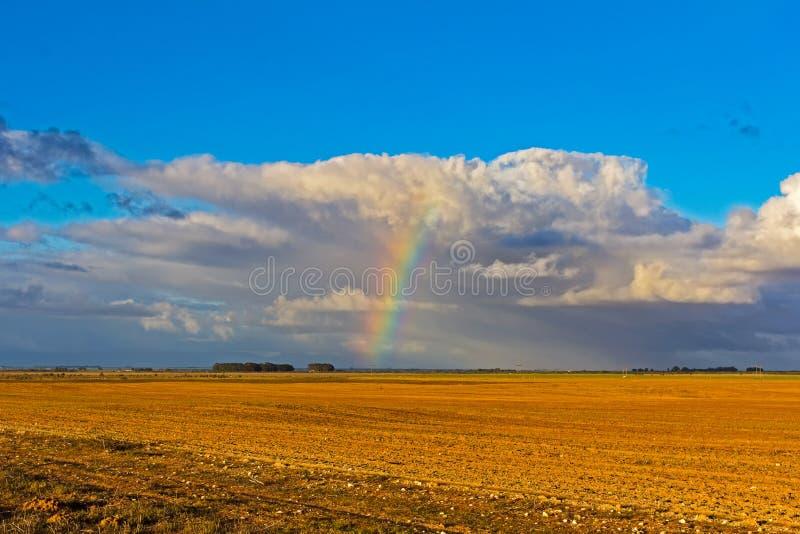 Regenboog en wolken over geploegd gebied stock foto's