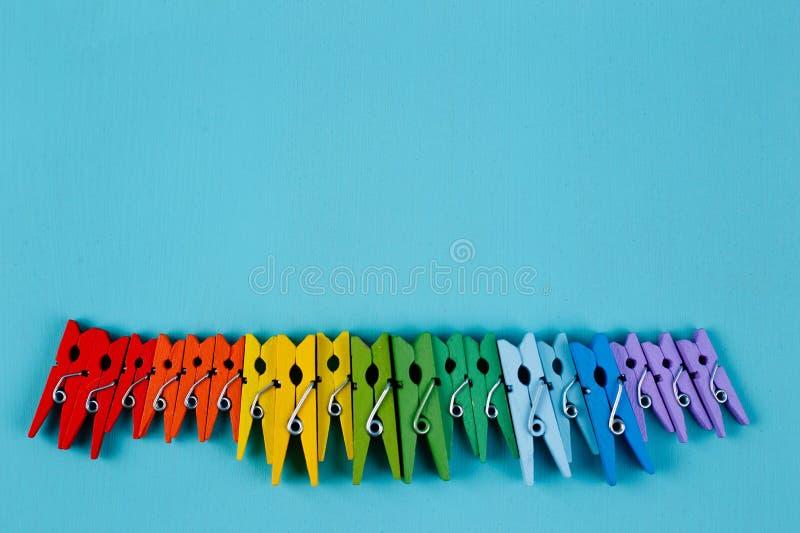 Regenboog heldere kleurrijke wasknijpers op blauwe achtergrond, exemplaar SP stock foto's