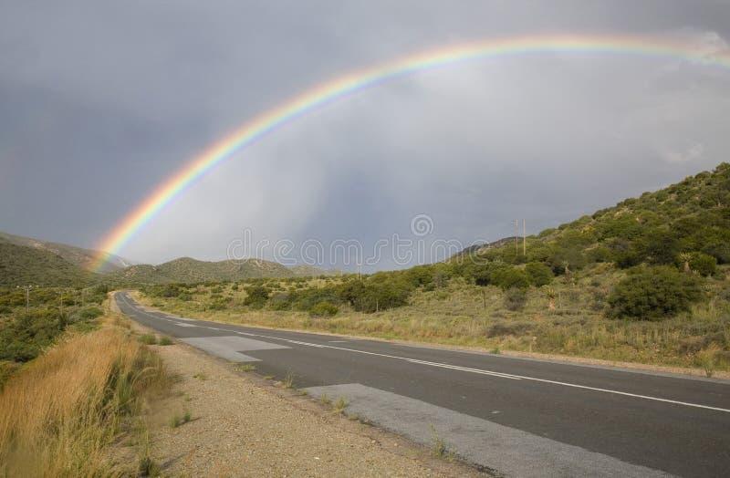 Regenboog het uitrekken zich over de weg stock afbeelding
