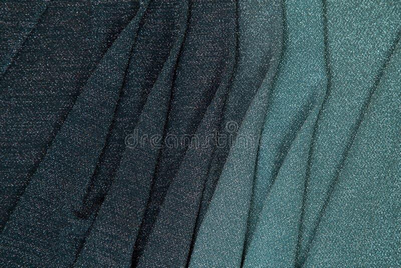 Regenboog lurex stof - de overgang van groen aan donker Bourgondi? voerde met verschillende vouwen royalty-vrije stock afbeeldingen