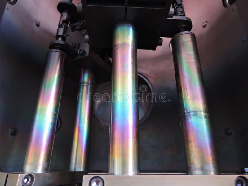 Regenboog op met een laag bedekte staalstaven binnen vacuümdepositokamer royalty-vrije stock foto