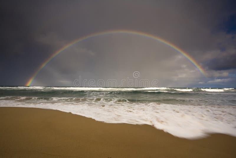 Regenboog op zee stock foto's